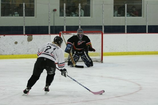Female hockey player approaching goal