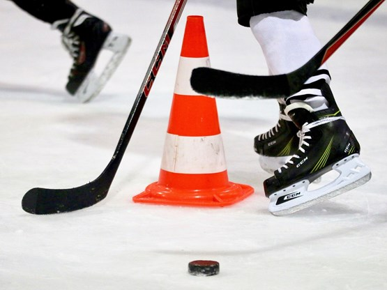 Hockey skates and sticks on ice with cone for drills