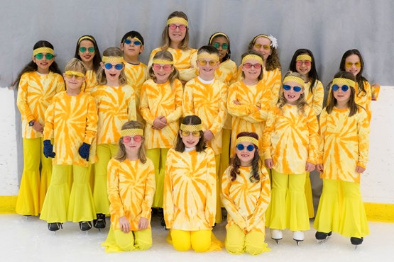 Ice skaters in yellow costumes posing for a photo