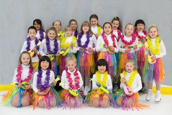 Child ice skaters in colorful costumes posing for a photo.